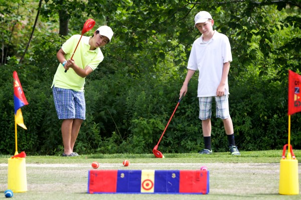 Kevin Ly, 13, (left) and Dana Hinchliffe, 13, practice chipping at the grand opening of the new South Course Clubhouse at the Riverside Golf Course in Portland Friday.