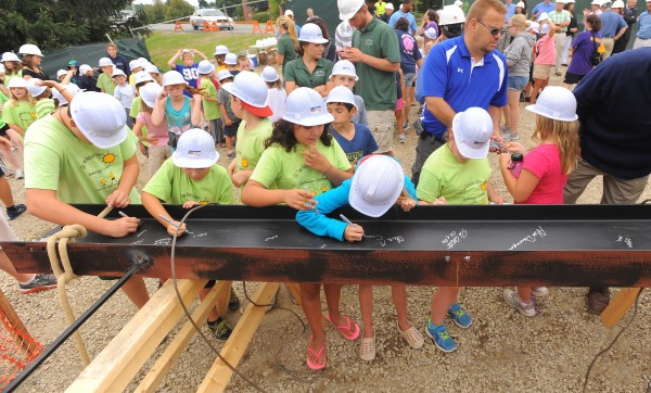 Children from Orono and Old Town were among those who signed a steel beam that was then hoisted into place during the topping-off ceremony for the new Emera Astronomy Center at the University of Maine in Orono Monday.
