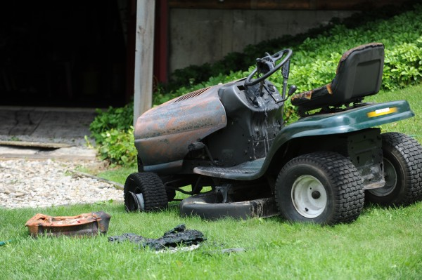 A lawn mower that was being worked on by 16-year-old Lucas Ashmore sits in the yard at 394 Jacob Buck Pond Road in Bucksport on Tuesday after the Bucksport fire department extinguished it.