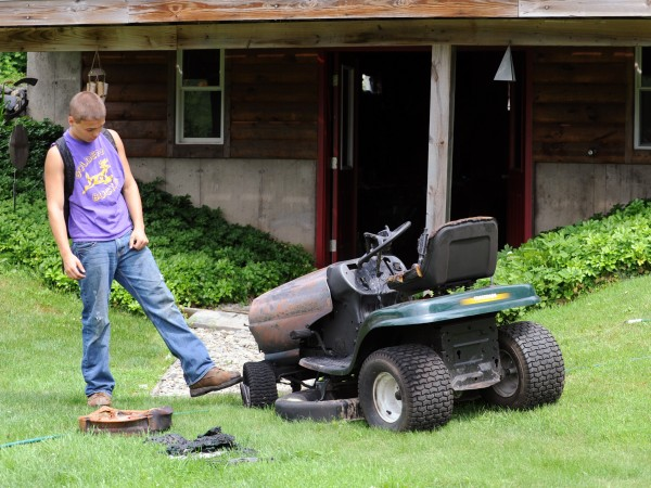 Lucas Ashmore, 16, kicks the tire of the lawn mower that he was working on that caught fire in the basement of the home of the owner.