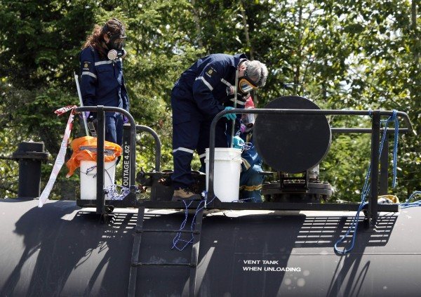 Inspectors from Transport Canada collect samples as part of their investigation in the train derailment in the town of Lac-Megantic, Quebec, Thursday.