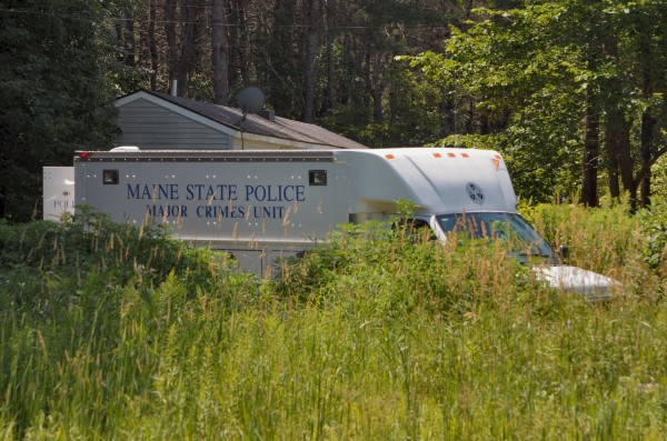 The Maine State Police Major Crimes Unit vehicle sits behind tall grass in front of the Main Street home where a man's body was recovered on Thursday in Detroit.