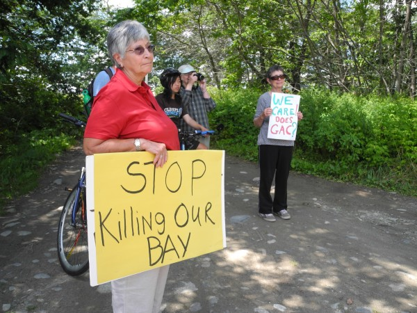 Environmental activists carrying signs listen Tuesday afternoon as Ron Huber of Friends of Penobscot Bay talked about possible contamination of the shoreline from a succession of fertilizer and chemical companies located in the same Kidder Point site for nearly 100 years.