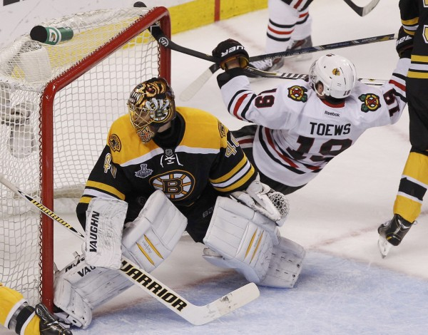 Chicago Blackhawks' Jonathan Toews (19) flies into the goal post behind Boston Bruins goalie Tuukka Rask during the third period in Game 6 of their NHL Stanley Cup Finals hockey series in Boston last month.