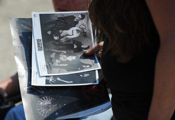 A heavy metal fan holds a stack of signed pictures during the RockStar Energy Drink Mayhem Festival in Bangor on Wednesday.