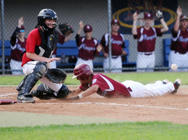 Bangor's Cameron Burpee slides into home plate as Holbrook's Tyler Williams bobbles the ball on Tuesday at Mansfield Stadium during third inning action in Bangor