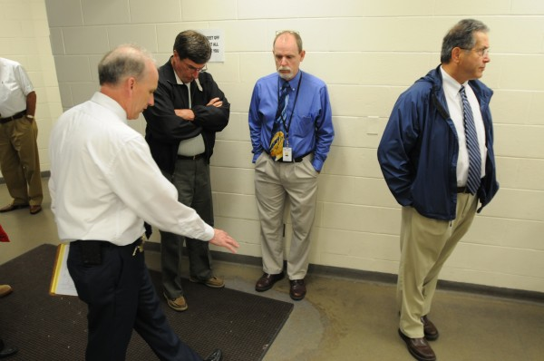 Penobscot County Jail Administrator Richard Clukey, left, offers a look at some of the concrete that is separating on the floor of the booking area at the jail on Thursday. With Clukey is Harry Sanborn, Penobscot County Administrator Bill Collins and commissioner Peter Baldacci.