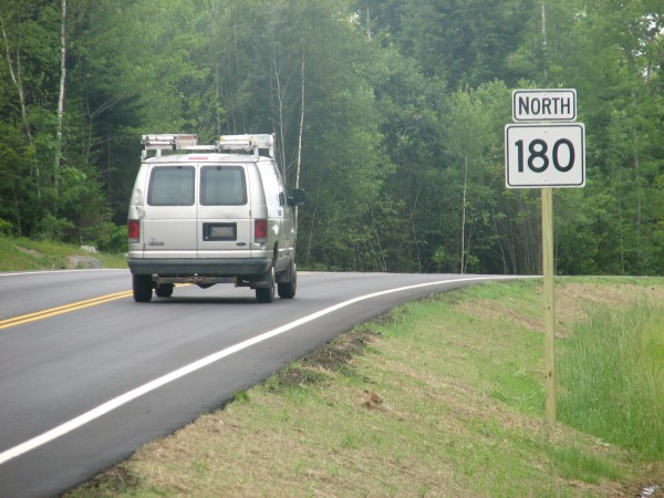 A van drives past a Route 180 sign on a new, two-mile section of the highway in Ellsworth that was opened to traffic on Monday, July 29, 2013. The new road was constructed so the highway could be rerouted from a structurally deficient bridge over a dam at the south end of Graham Lake.