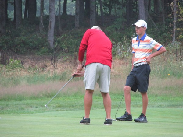 Ralph Michaud (left) putts as Drew Powell looks on Wednesday during the Maine Amateur Championship in Manchester.