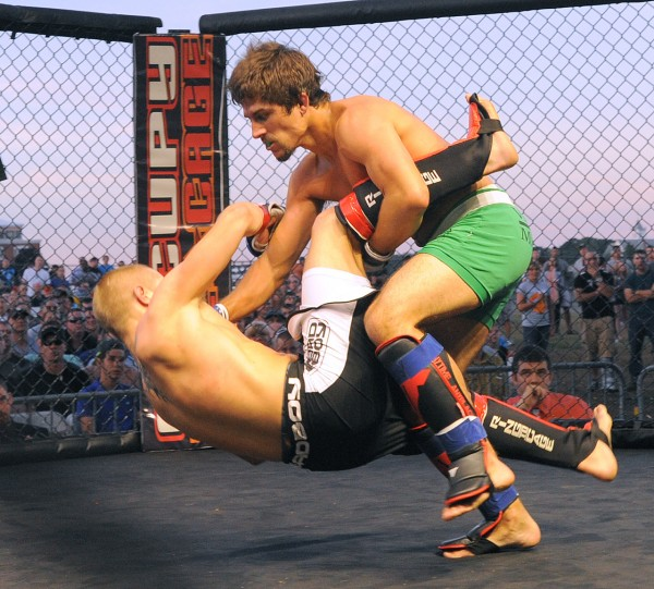 Stephen Desjardins (right) of Brewer takes down Trevor Hebert of Topsham during their MMA fight at the Bangor Waterfront on Friday. Hebert won the fight.