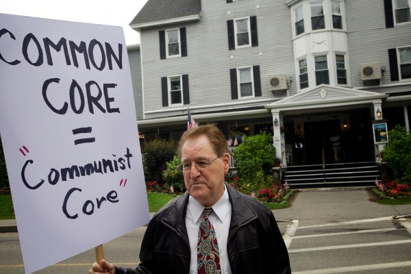 Lone protester Steve Schran, a retired music teacher from  New Gloucester, holds a sign outside the Nonantum Resort in Kennebunkport on Tuesday as a Paul LePage re-election fundraising event, featuring keynote speaker Jeb Bush, commenced inside.