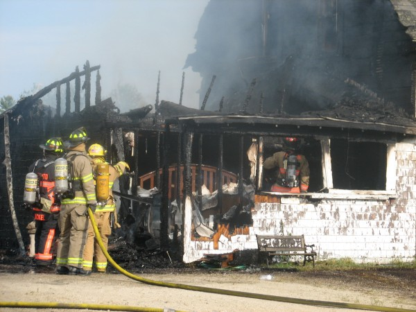 Firefighters check out the smoldering remains of a house that caught fire Thursday, July 18, 2013, on Webb Pond Road in Eastbrook.