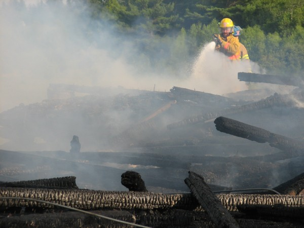 Firefighters spray water on the burning remains of a barn that caught fire Thursday, July 18, 2013, on Webb Pond Road in Eastbrook.