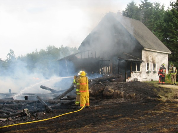 Firefighters spray water on the burning remains of a barn that caught fire Thursday, July 18, 2013, on Webb Pond Road in Eastbrook. The cause of the fire, which spread to and destroyed a nearby house, has not been determined, according to firefighters. Seven Hancock County towns sent firefighters to help put out the blaze.