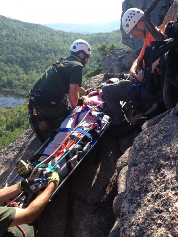 Rescue personnel help lift a 62-year-old woman to safety along the Beehive trail in Acadia National Park on Wednesday after the woman slipped on metal rungs on the trail and fractured her leg, according to Acadia officials.