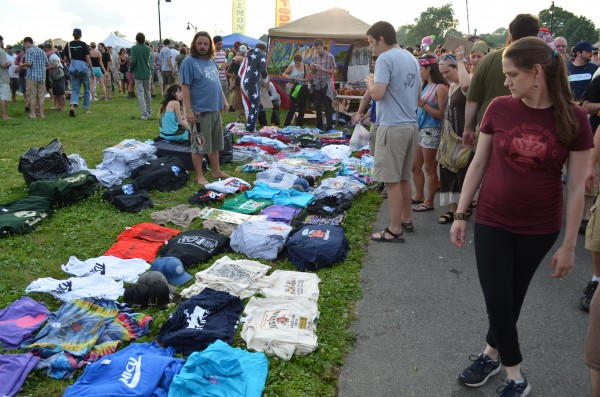 A woman glances at rows of T-shirts for sale along the Bangor Waterfront before the Phish concert on Wednesday.