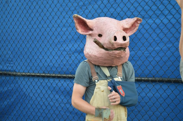 A man wearing a papier-mache pig's head waits in line to get into the Phish concert on Wednesday.