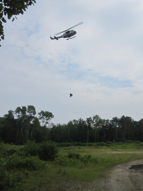 Dangling from a 50-foot static line attached to a Maine Forest Service helicopter, the injured Edward Hamara and Maine Forest Service Ranger Thomas Liba took a five-minute trip down from nearly 4,000 feet to waiting rescuers, said Millinocket Fire Chief Andrew Turcotte.