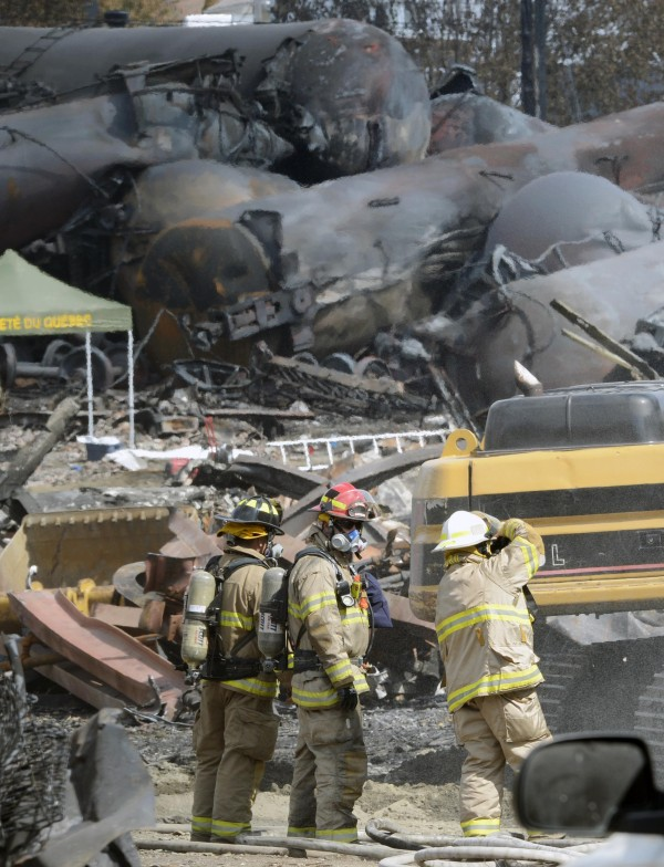 Firefighters looks on while working on the site of the train wreck in Lac Megantic, July 16, 2013.