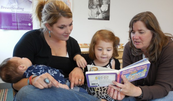 Ashli Bickford (left) reads a book with her two youngest children during a home visit with Parent Education Professional, Claudia Williamson (right)