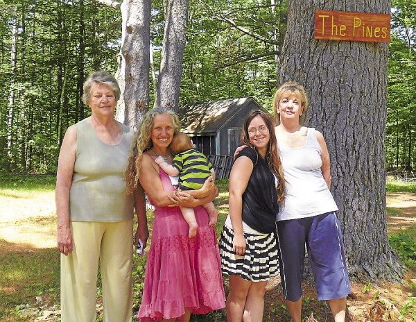 Pausing in The Pines from a stroll around the grounds of Camp Etna are (from left) Carol Mead, Etna Spiritualist Association trustee, Diane Jackman Skolfield holding baby Guy Couture, Bethany Couture (Guy's mother), and Shirley Boyens. The women will attend association programs being held through August at Camp Etna.