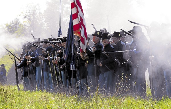 Smoke enshrouds Civil War re-enactors portraying Union infantry at Perryville, Ky. on Saturday, Oct. 6, 2012. During a battle, the flag bearers and color guard stood in the center of a regiment's front line to indicate where the unit was deployed. At Gettysburg on July 2, 1863, the 17th Maine Infantry Regiment sent a 10-soldier color guard into battle at the Wheatfield; only three members of the color guard survived unscathed.