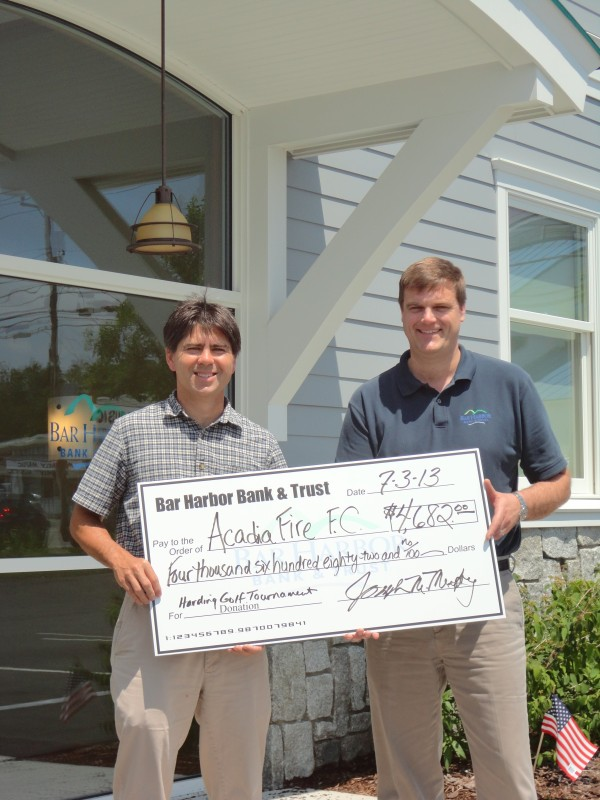 (left to right): Michael Curless of Acadia Fire accepts a check for $4,682 from Sam McGee of Bar Harbor Bank & Trust, representing the planning committee for the Bank's 20th Annual David R. Harding Memorial Charity Golf Tournament played at Kebo Valley Golf Club on June 4.  This year's tournament benefitted Acadia Fire FC, MDI Soccer Club.  The funds will go toward providing scholarships, purchasing equipment such as soccer balls and portable goals, and subsidizing coach education.