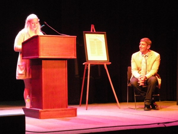 Megan Rickard, Trekker Alumna, Class of 2013 at the podium, pictured with Inaugural Poet Richard Blanco.