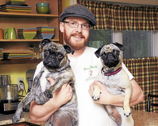 Dog Wok owner and Bangor personal chef Carl Maxwell makes gourmet pet food for his clients that is full of real ingredients and nutrition. Pictured with him is Fenway (aka Fenway Frank), a Boston terrier and pug mix, and Remi (aka Rem Dog) a pug. Maxwell's business not only includes pet food, but also dog walking.