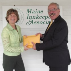 Sue Inches, Executive Director of Habitat for Humanity of Maine, accepts donation checks from Greg Dugal, Executive Director of Maine Innkeepers Association for their annual Hospitality for Habitat fundraiser.