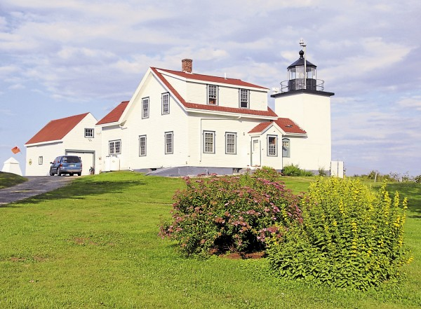 The evening sun illuminates Fort Point Lighthouse and nearby flowers in Stockton Springs on July 21.