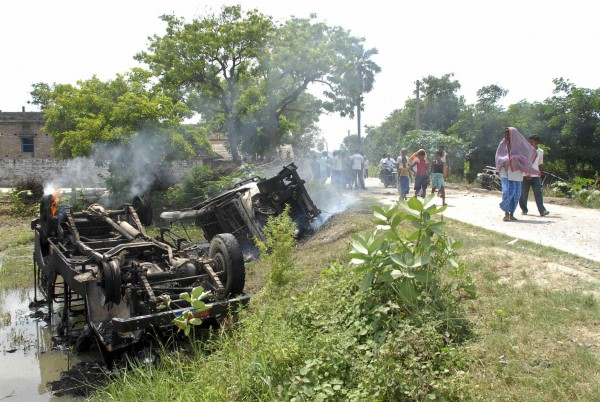 People walk past overturned vehicles that was burnt by protesters as they campaign against contaminated meals that were given to children, at Chapra in the eastern Indian state of Bihar July 17, 2013.