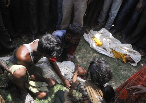 A man weeps while holding the body of his child who died after consuming contaminated meals given to children at a school on Tuesday at Chapra in the eastern Indian state of Bihar July 17, 2013. At least 25 Indian children died and dozens needed hospital treatment after apparently being poisoned by a school meal, sparking violent protests and angry allegations of blame.