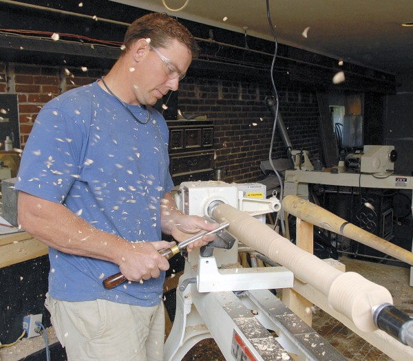 Jesse LaCasse uses a woodcarver's knife to shape a bat as it turns on a Jet lathe at LaCasse Bat Co. in Skowhegan.