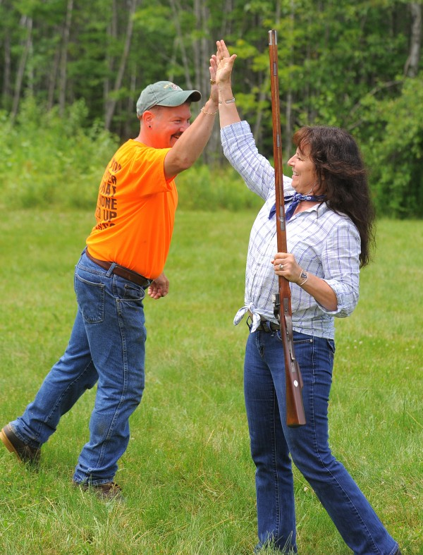 Jeff Durkee (left) celebrates with Karen Moffett after she became the first person to win a match Durkee established. The idea was to shoot at a small spoon a button and a suspended ring and hit each one on the first try from about 20 yards away. Moffet was the first one to be able to do so, since Durkee came up with combination about three years ago. It was so challenging that he promised $300 to the first person who is able to complete the match.