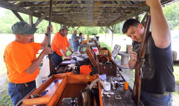 Jeff Durkee (left) and his son Wyatt (right) clean their rifles at the Penobscot Longrifles shooting range in Stetson. The members spend a great deal of time maintaining their guns that are exact replicas of rifles used in the 1700s and early 1800s. The old-fashioned guns also present technical challenges as they must be properly maintained and tuned to fire in varied weather conditions.