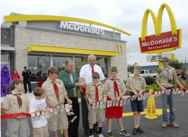 McDonald's owners/operators Marty Eckmann (fourth from left) and Gary Eckmann cut a dollar bill-festooned ribbon at the grand opening of the new Hogan Road McDonald's in Bangor. The Eckmanns were assisted by Cub Scouts' Pack 21, Dedham-Holden, and Boy Scouts' Troop 44, Orrington. The new restaurant replaced an existing McDonald's torn down this past spring.