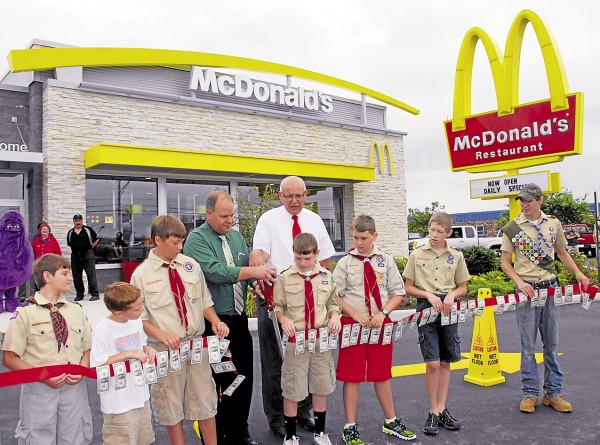 McDonald's owners Marty Eckmann (fourth from left) and Gary Eckmann cut a dollar bill-festooned ribbon at the grand opening of the new Hogan Road McDonald's in Bangor. The Eckmanns were assisted by Cub Scouts' Pack 21, Dedham-Holden, and Boy Scouts' Troop 44, Orrington. The new restaurant replaced an existing McDonald's torn down this past spring.