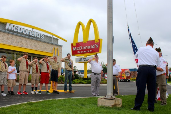 Members of Boy Scout Pack 21 of Dedham and Holden stand in salute as Bangor VFW Post 1761 Honor Guard raise the United States flag during the McDonald's restaurant's reopening on Hogan Road Thursday.