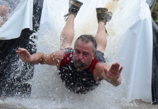 An unidentified racer slides on his belly into the pool at the end of the last obstacle on the Tough Mountain Challenge course at Sunday River on Saturday.