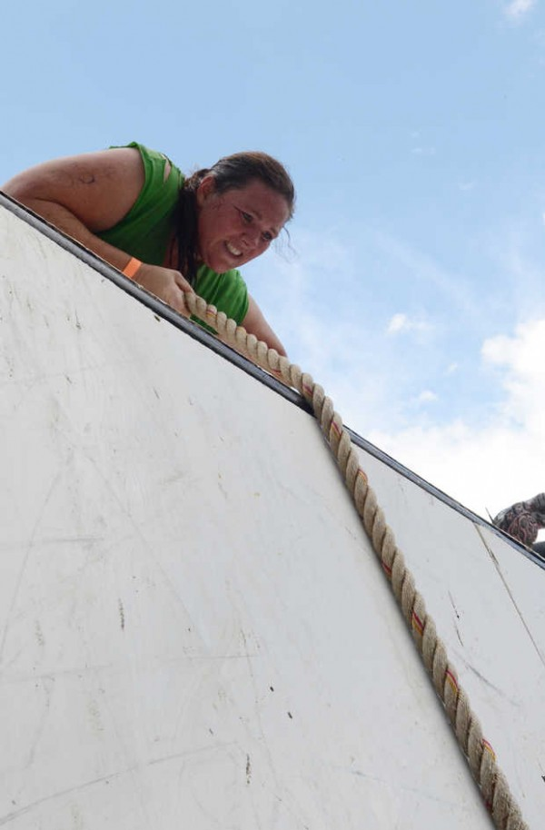 Caroline Perkins of Turner makes her way over the top of an obstacle at the Tough Mountain Challenge at Sunday River in Newry on Saturday. About 3,000 racers took part in the event.
