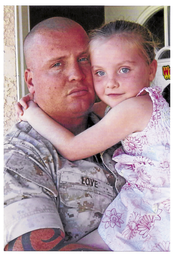 Marine Master Sgt.Ryan C. Love holds his daughter, Liberty Ryan. Love died unexpectedly in July 2012.