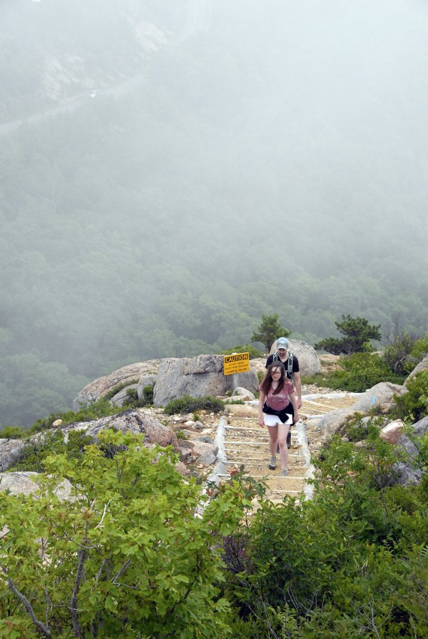 Hikers Meghan Carter and Brent Walter reach the upper ledges of South Bubble after ascending the steep trail that rises from Jordan Pond (background) in Acadia National Park. Fog surrounds South Bubble and obscures the nearby Park Loop Road.