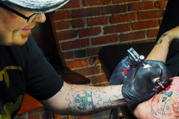 Matthew Moore, of Forecastle Tattoo applies a tattoo on Sara Weeks of Bangor,Thursday afternoon, at his shop on State Street hill in Bangor.