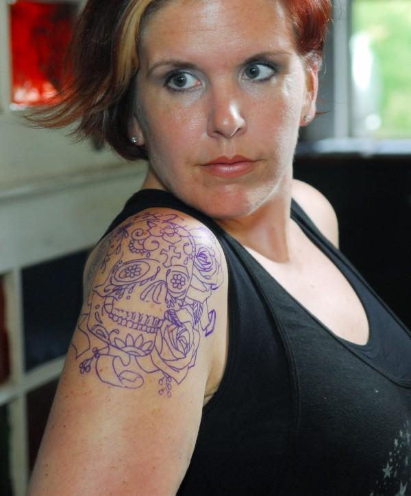 Sara Weeks of Bangor, eyes the steinole of the Tattoo called Sugar Skull in the mirror Forecastle Tattoo in Bangor.