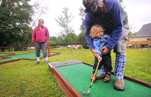 Two-year-old Milo Slevin gets some help from his father, Matthew Slevin, while playing minigolf at Pleasant Hill RV Park & Campground in Hermon on Tuesday afternoon. Milo left his home in Wolcott, Colo., four weeks ago with his mother, Lauren Thomas (left) and father to make his way to the fifth Phish show of his life. Matthew is a longtime follower of the band and this year the family decided to make a road trip of following Phish.