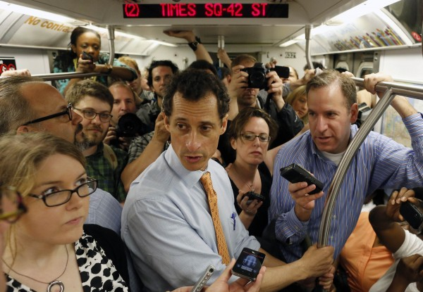 Former U.S. Representative and New York City mayoral candidate Anthony Weiner (center) talks with reporters while riding the subway between campaign events in New York in this file photo taken May 23, 2013. Weiner confirmed on Tuesday that some newly revealed sexually explicit online chats and photos published this week by a gossip website were sent by him.