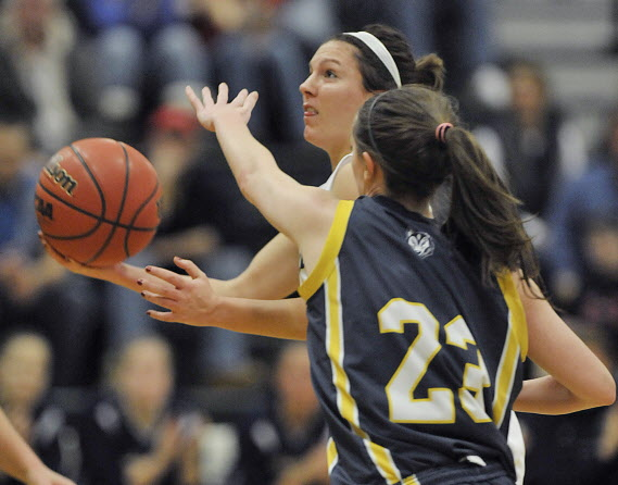 Husson University's Amanda Gifford (14) drives by the University of Southern Maine's Erin McNamara during a game in January 2012 in Bangor. Gifford has been named Hermon High School's girls basketball coach.