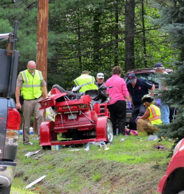 Rescue workers attend to one of the victims who were on the GoldWing Honda SE red motorcycle that narrowly missed a telephone pole when the Honda went off the road near 747 Waterford Road.