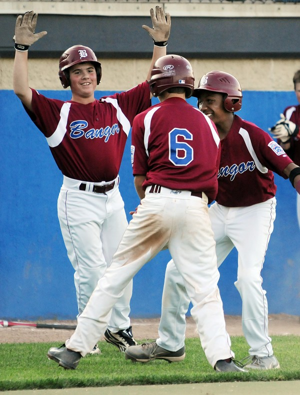 Bangor's Jessie Colford, George Payne and John Clement celebrate Payne's score during 2nd inning against Hampden on Monday at Mansfield Stadium.